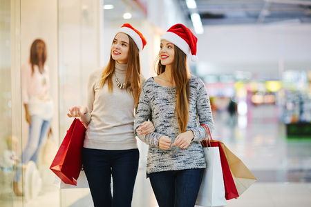 Christmas girls buying presents in shopping-center
