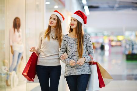 De meisjes van Kerstmis cadeautjes kopen in winkelcentrum-center Stockfoto - 65134621