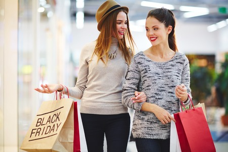 shoppingbag: Pretty girls with paperbags taking walk in the mall Stock Photo