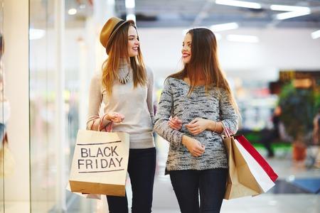 Los compradores llevando bolsas de papel y hablando a la venta el Viernes Negro Foto de archivo - 65134715