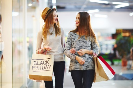 Shoppers carrying paperbags and talking at Black Friday sale