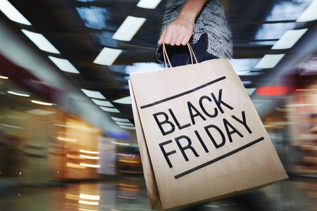 paperbag: Low section of shopaholic with black friday paperbag during buying craze Stock Photo