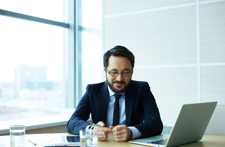 employer: Young employer in suit sitting in office Stock Photo