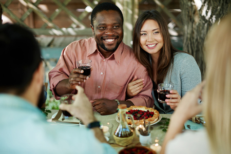 Multi-ethnic couple cheering with glasses of red wine during Thanksgiving dinner photo