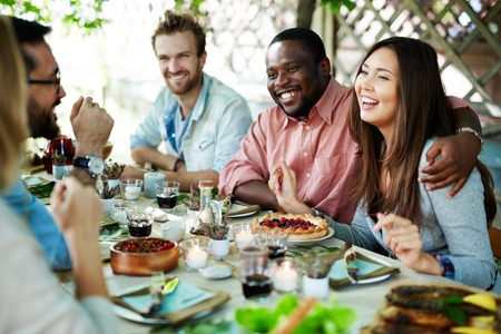 Joyful couple and their friends talking by festive dinner photo