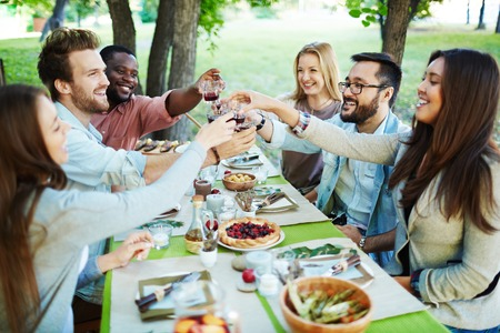 altogether: Group of multi-ethnic friends toasting with red wine Stock Photo