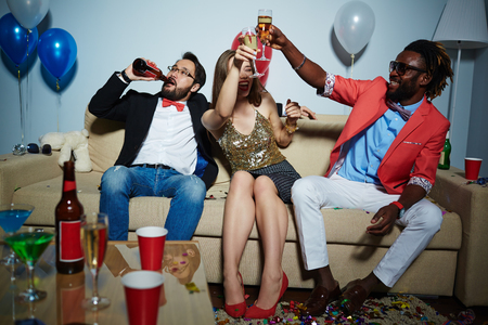 Young intercultural couple toasting with flutes of champagne at party
