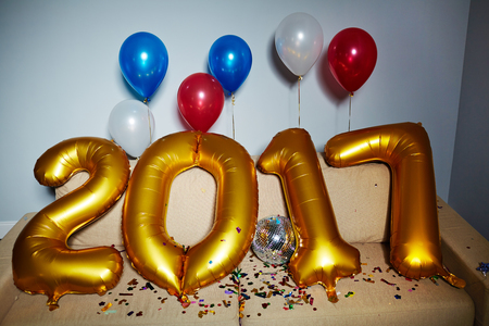 newyear: Balloons in form of numbers of the next year, traditional balloons, disco-ball and confetti on sofa Stock Photo