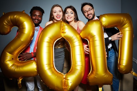 Ecstatic friends holding number of the next year