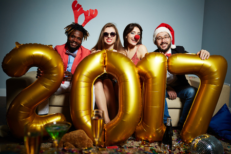 next year: Friends in Christmas attire holding golden number of next year Stock Photo