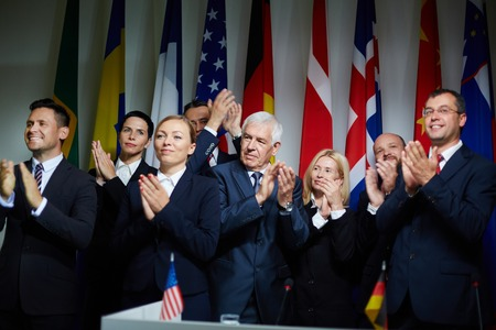 delegates: Group of formal-dressed confident delegates smiling and applauding during summit on background of national flags