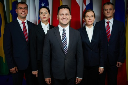 delegates: Group portrait of formal-dressed male and female delegates with confident smiling executive on foreground looking at camera on background of national flags Stock Photo