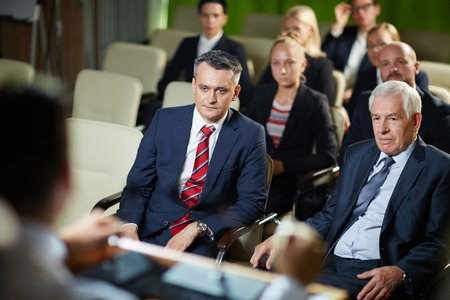 Group of business people sitting and listening attentively to the blurred speaker in conference room at the meeting, two confident formal-dressed men on foreground photo