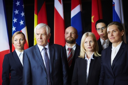 attentively: Group of formal-dressed  male and female delegates standing on background of national flags at summit, listening to someone attentively, some of them looking puzzled