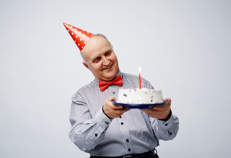 party pastries: Happy senior man looking at tasty birthday cake with candle
