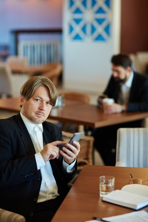 celphone: Elegant businessman sitting in cafe and writing sms