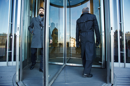 Revolving door with elegant businessmen inside Stock Photo