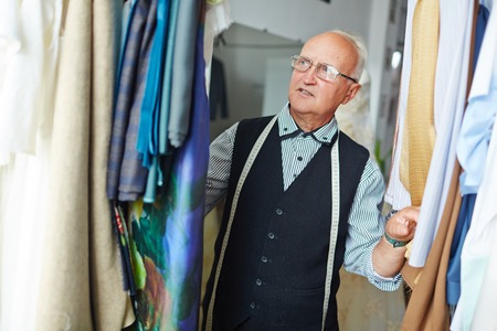 finding out: Portrait of elegant looking mature tailor with measuring tape on his neck looking through fabrics for finding out necessary one in his workshop Stock Photo