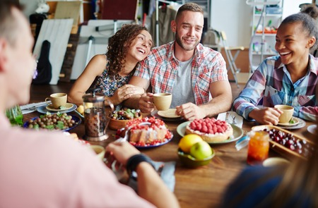 Laughing friends talking by Thanksgiving table Stock Photo