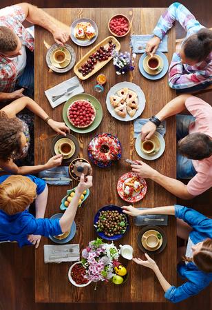 personas comiendo: Grupo de jóvenes que se sientan por la mesa de fiesta y comer la comida de Acción de Gracias
