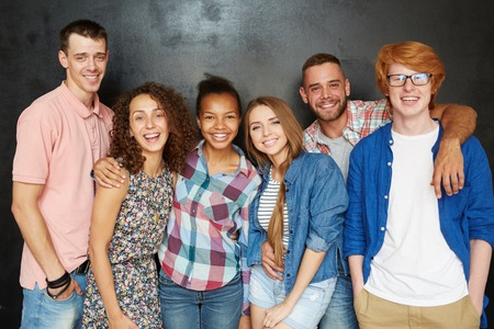 group of young adults: Carefree friends in casualwear looking at camera with smiles