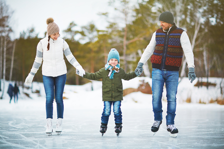 Family portrait of cheerful young parents looking at their son with smile and holding his hands while skating on winter park rink, blurred background Standard-Bild