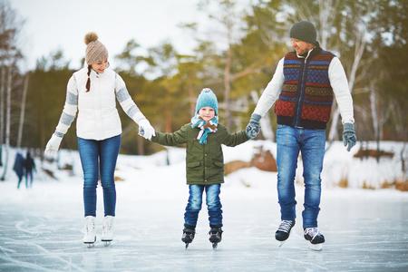Retrato de la familia de los padres alegres jóvenes que miran a su hijo con la sonrisa y la celebración de sus manos mientras que el patinaje en el parque de invierno pista, fondo borroso Foto de archivo
