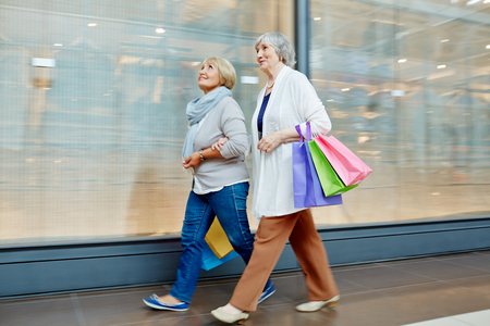 Two pensioners walking down contemporary mall