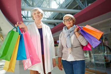 Two retired friends with paperbags looknig at camera in retail-market Stock Photo