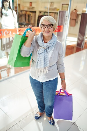 shoppingbag: Mature shopper with purchases standing in shopping center