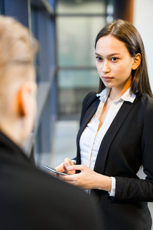 men and women: Confident young woman listening to her colleague Stock Photo
