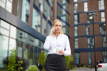 confident business woman: Businesswoman speaking to buyer on mobile phone outdoors