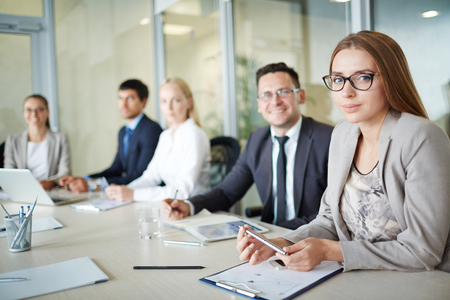Young businesswoman looking at camera on background of her co-workers
