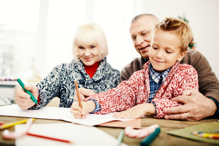 Cute child and his grandparents drawing with highlighters photo