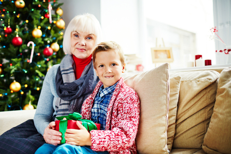 Mature female with her grandson sitting by Christmas tree photo