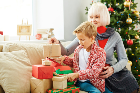 Boy and his grandmother preparing xmas presents for family photo