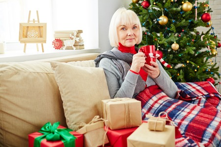 Senior woman with drink looking at camera while having rest at home photo