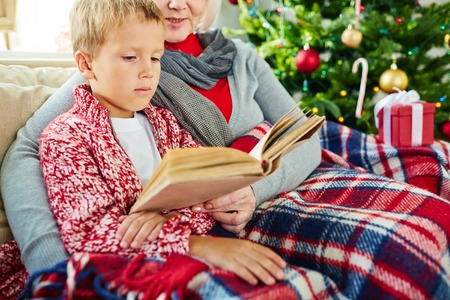 Adorable kid reading stories in book with his grandmother photo