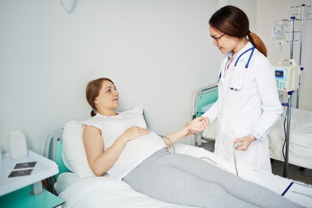 Pregnant woman lying in bed while doctor measuring her blood pressure Stock Photo
