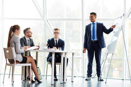 young businessman: Young man explaining financial statistics to managers Stock Photo