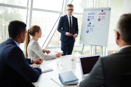 proficient: Young businessman standing by whiteboard in front of his co-workers Stock Photo