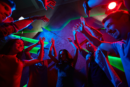 adult entertainment: Guys and girls raising hands during energetic dance in night club