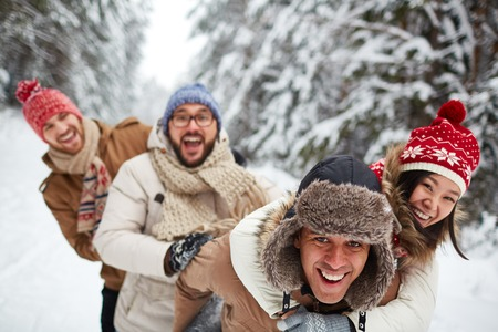 wintery: Ecstatic young couple and their friends enjoy wintery day in park