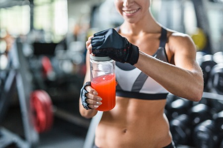 Refreshments: Sporty woman opening bottle with kissel after training