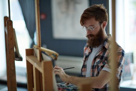 Geïnspireerde jonge man tekenen ruw ontwerp op papier royalty