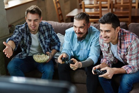 ardor: Three happy guys playing video game in team Stock Photo