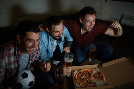 ecstatic: Ecstatic men expressing triumph during football match broadcast Stock Photo