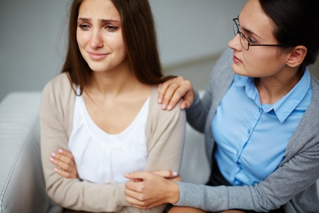 Psychologist supporting depressed girl during session photo