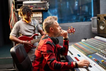 soundboard: Deejay looking at screen while regulating volume on soundboard Stock Photo