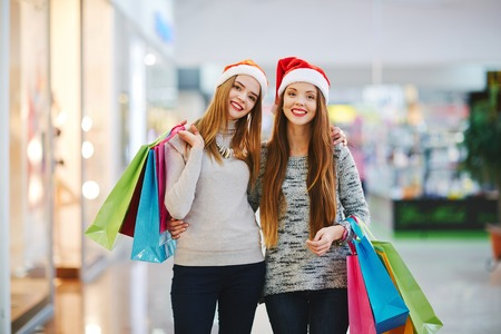 Two happy shopaholics looking at camera at Christmas sale Stock Photo